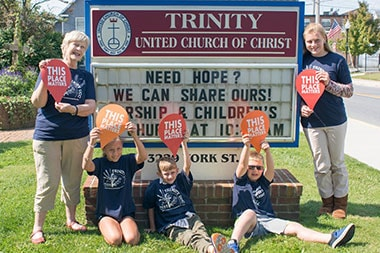 "Trinity UCC Members Holding Up ""This Place Matters"" Signs"